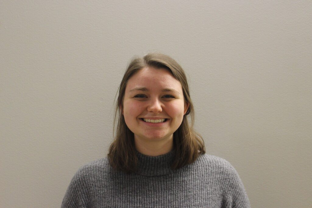 A mid-torso picture of a college-age white girl with her hair up and a gray sweater on standing against a gray wall